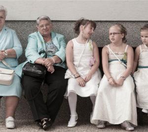 Alte und junge Frauen sitzen auf einer Bank